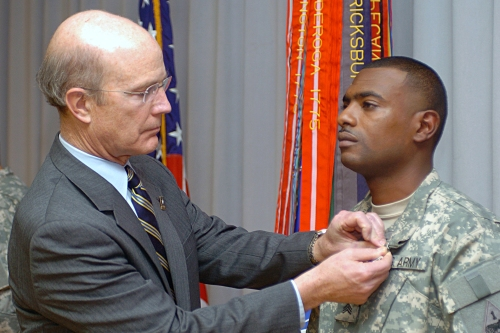 U.S. Army Secretary Pete Geren presents the Purple Heart to Sgt. Justin Smith, a team leader for 1st Platoon, Company B, 70th Engineer Battalion, during an awards ceremony at Walter Reed Army Medical Center, Jan. 30, 2009. This marks the second time Smith has been awarded the Purple Heart.   U.S. Army photo by Staff Sgt. Matthew Clifton